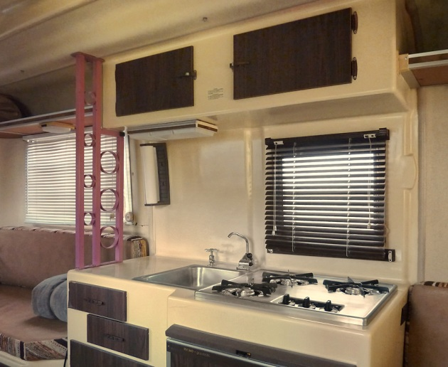 The galley is equipped with a 3-burner propane cooktop, a 3-way refrigerator, and small sink with water hand-pumped from the onboard tank or pressure water from an outside hookup.